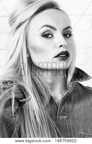 girl or beautiful cute woman fashion model with blond hair and red lips in sexy denim blue jeans clothes poses on white brick wall black and white