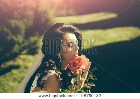 Woman with dress and veil at red rose. Bride with long brunette hair with flower. Wedding holiday celebration. Girl with fashionable makeup in earring. Beauty and fashion.