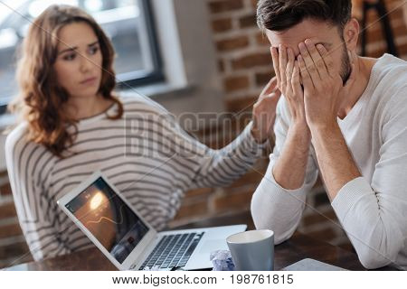 I have lost. Depressed cheerless handsome man sitting at the table and covering his face while being consoled by his girlfriend