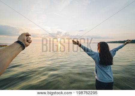 first person view , man looking on girl that sitting on old boat at the beach and looking on sunrise