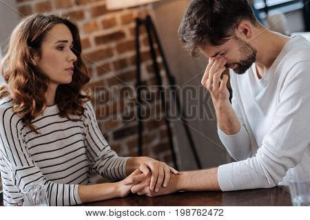Everything will be okay. Beautiful pretty caring woman holding her boyfriends hands and looking at him while showing her support