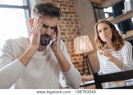 Stop shouting. Unhappy nice handsome man holding his temples and rubbing them while having a quarrel with his girlfriend