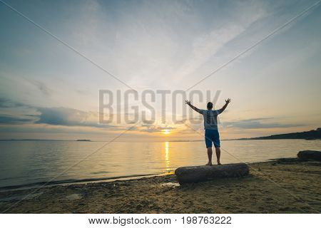 man on sand beach looking on sunrise with hands up