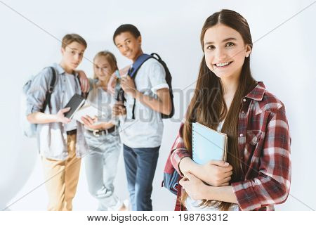 Smiling Teenage Girl With Notebook In Hands Looking At Camera With Multicultural Students Behind Iso