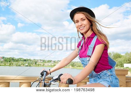 Attractive young woman smiling happily to the camera while cycling at the park copyspace beauty recreation weekend holidays relaxing enjoyment recreation beauty youth.