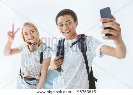 Portrait Of Multicultural Teenagers Taking Selfie Together On Smartphone Isolated On White