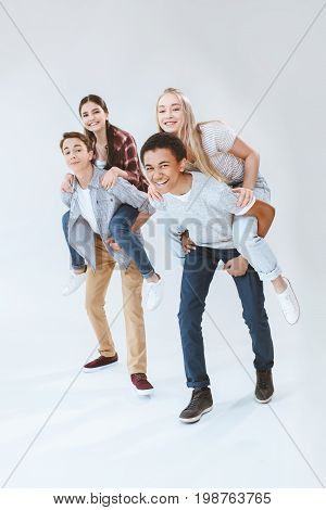 Happy Multicultural Boys And Girls Piggybacking Together Isolated On White