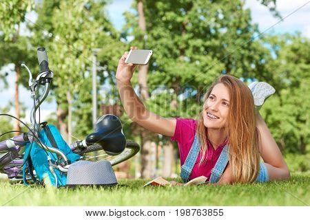 Attractive young woman taking a selfie with her smart phone while lying on the grass near her bicycle technology gadget mobility connection connectivity social media communication lifestyle.