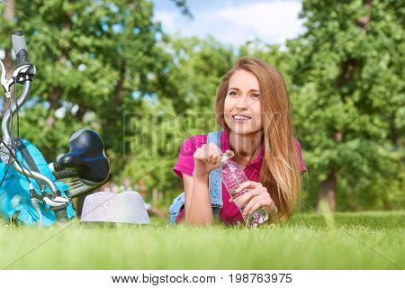 Shot of a gorgeous young woman having water while lying on the grass at the local park after cycling copyspace aqua hydration healthy health healthcare active fitness lifestyle positivity vitality.