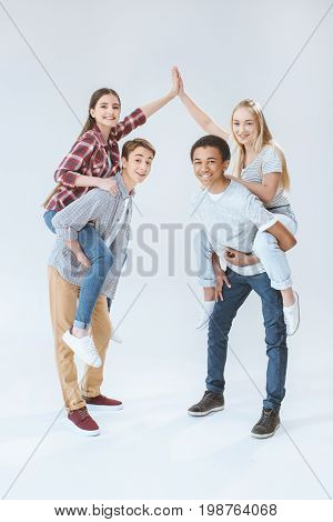 Girls Giving High Five While Piggybacking With Multicultural Boys Isolated On White