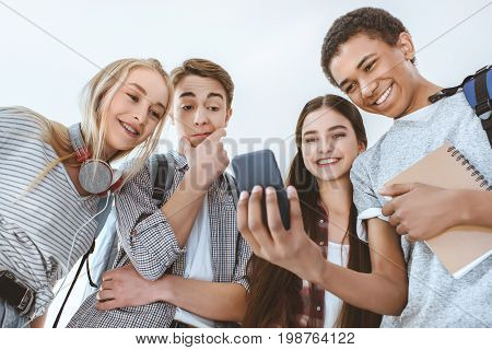 Low Angle View Of Multicultural Smiling Teenagers Using Smartphone Together Isolated On White