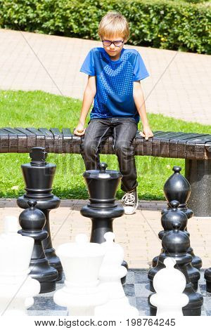 Chess game with giant chess piece. Boy playing strategic outdoor game on black and white chess board