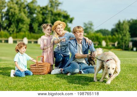 Happy Young Family With Dog Resting On Green Grass At Picnic