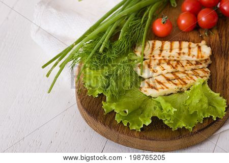 Grilled slices of homemade halloumi cheese with green salad fresh herbs and organic tomatoes.Fried halloumi cheese with grill marks on white wooden background top view