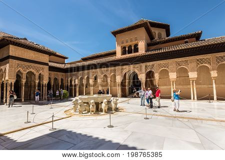 Granada Spain - May 19 2014: Tourists in the Court of the Lions in the Alhambra palace in Granada Spain - masterpiece of moorish architecture (14th century).