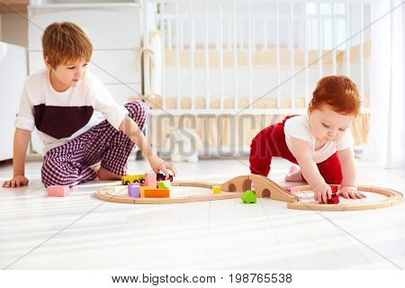 Cute Kids, Brothers Playing Together With Wooden Toy Railway In Nursery Room