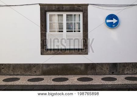 Window on a white wall and a traffic sign. Footpath with contrast pattern. Ponta Delgada Sao Miguel Azores Islands Portugal