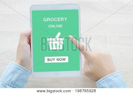 Hand using tablet with grocery online on screen device background grocery online business and technology digital marketing concept