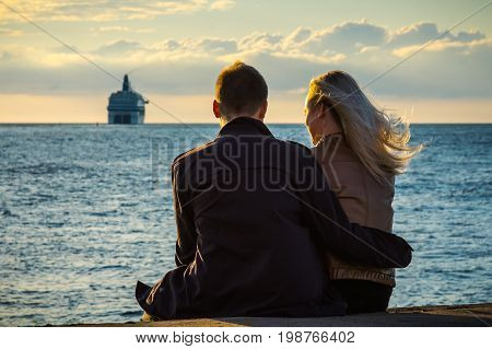 Young people in love look at the ferry leaving for the Baltic sea romantic background