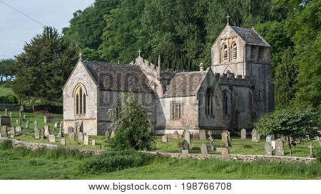 A typical english country scene with old village church set in cemetery surrounded by fields and trees