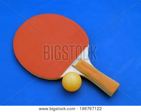 red table tennis (ping-pong) racket with orange ball on blue table, indoor sports equipment