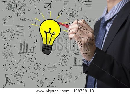 Business hand drawing light bulb with graph. concept of new idea with innovation and creativity.