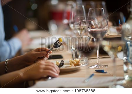 Anonymous people enjoying wine and drinks while sitting at table at party.