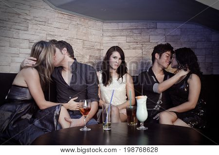 couples making out in a nightclub. a pretty but single woman is sitting between them, looking rather sad. intentionally desaturated.