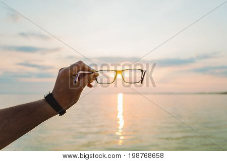 first-person view sunrise through eyeglasses, hold glasses in hand