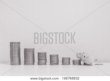 Closeup pile of coin start from low to high with three little pig doll walk to the top of coin on desk and wallpaper textured background with copy space in saving money concept in black and white tone