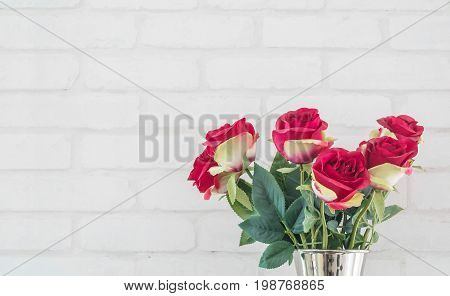 Closeup artificial fabric red rose flower for decorate on white brick wall textured background with copy space