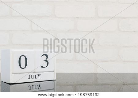 Closeup white wooden calendar with black 3 july word on black glass table and white brick wall textured background with copy space selective focus at the calendar