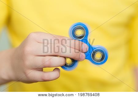 A boy is playing a popular toy fidget spinner in his hands. Stress relief. Anti stress and relaxation fidgets, spinner for tired people. Boy playing with a fidget spinner.