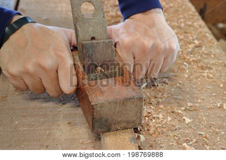 Hand of worker planing a plank of wood using a hand planer