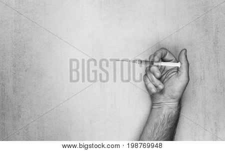 Male hand with disposable syringe for injection on a gray background black and white photo. mock up for text phrases lettering