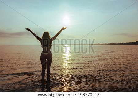 woman standing on the beach in sweemuit with sexy ass hands up,