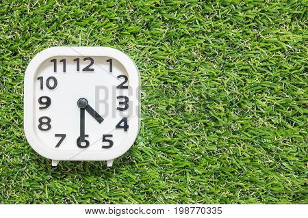 Closeup white clock for decorate show a half past four o'clock or 4:30 p.m. on green artificial grass floor textured background with copy space