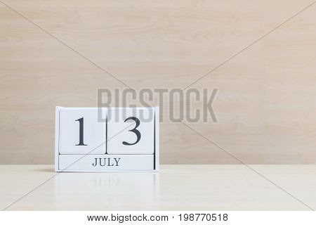 Closeup surface white wooden calendar with black 13 july word on blurred brown wood desk and wood wall textured background with copy space selective focus at the calendar