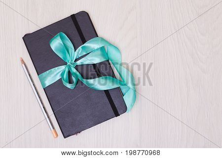 Gift with ribbon on the table. Pencil and sketchbook.