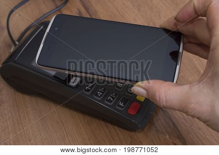 People and modern technology concept. Close up of businessman's hand holding copy space smart hpone close to POS-system while paying for bill after lunch at restaurant. Point of sale terminal
