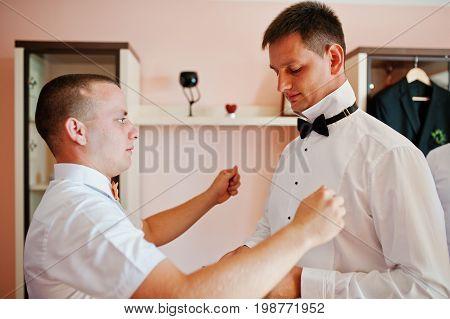 Helpful groomsmen or bestmen helping groom to get ready for his wedding.