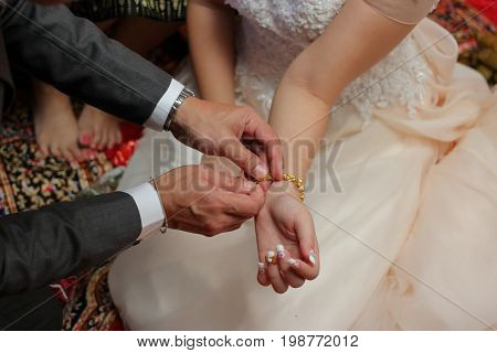 Groom put the gold bracelet on bride's wrist. Concept of marriage