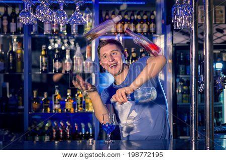 Young barman juggles bottles. Flaring. Club life