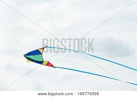 single colorful kite flying in cloudy sky at daytime