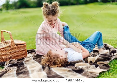 Cute Little Siblings Having Fun Together While Resting On Plaid At Picnic