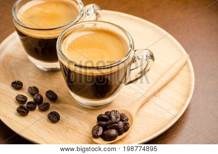 Two cups of hot espresso coffee and roasted coffee bean on wooden plate for drink in the coffee shop