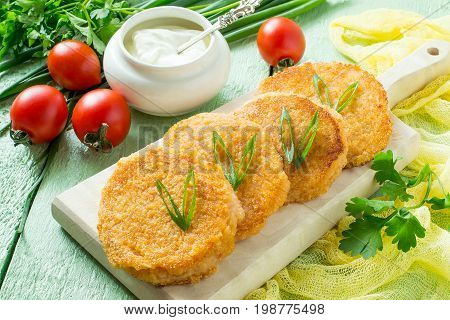 Tasty onion cutlet fresh vegetables (tomatoes parsley green onions) and sour cream on green wooden table. The concept of dietary and vegetarian food. Healthy food