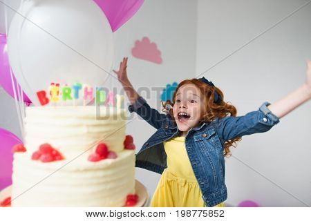 Cute Happy Red Haired Girl With Raised Hands Jumping Near Birthday Cake