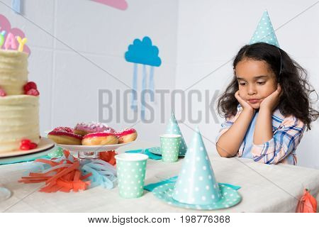Upset Little African American Girl Sitting Alone At Birthday Table