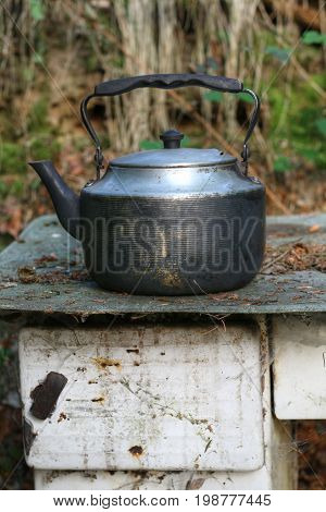 Detail of the old and worn teapot on old stove
